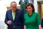 In this March 12, 2020, file photo Senate Minority Leader Sen. Chuck Schumer of N.Y., and House Speaker Nancy Pelosi of Calif., walk together on Capitol Hill in Washington. Schumer said Friday that more money is needed for widespread, accessible testing for the coronavirus before the economy can be reopened with confidence.