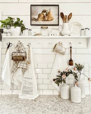 """Subway tile in the kitchen provides a timeless backdrop for new and old white wares and wooden collectibles. Open shelving in kitchen are both practical and pretty. """"I grab scissors and twine almost every day,"""" she says."""