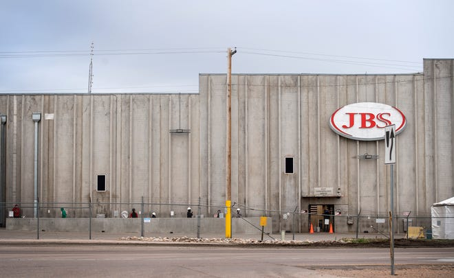 People walk outside at JBS meat packing plant in Greeley, Colo. on April 15, 2020. The plant has experienced 102 COVID-19 cases among its employees, four deaths and one county public health order as of April 16, 2020. JBS announced the facility would not reopen until April 24. A total of 60 people at JBS in Gun Plain Township, Mich., tested positive for the virus, according to Allegan County Health Department spokesperson Lindsay Maunz.