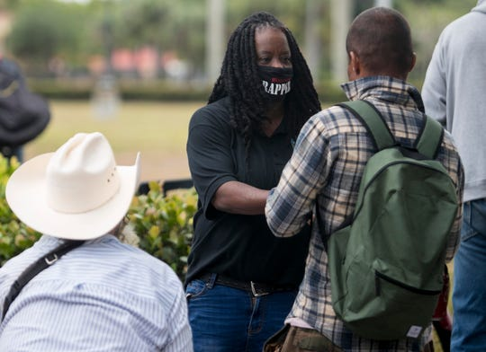 Ramona Miller of A Voice in the Wilderness hands out meals to people at City of Palms Park on Thursday, April 16, 2020.