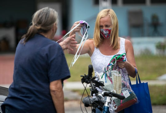 Kerry Constantine of Blankets and Blessings hands out masks to people getting a meal at City of Palms Park on Thursday, April 16, 2020, in Fort Myers.