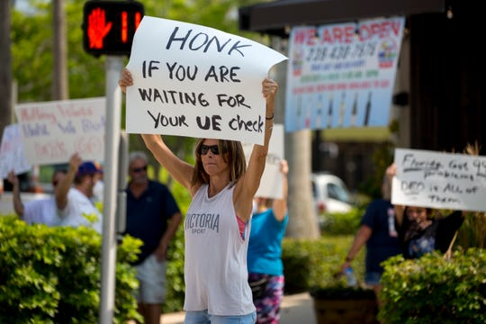 Holly Emmons, a restaurant employee who was laid off, protests with others in downtown Naples on Friday, April 17, 2020. The group came out to protest the Florida unemployment system. Many have been out of work for at least a month and haven't gotten an unemployment check yet.