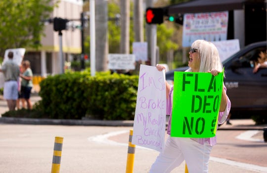 Holly Harding of Naples was laid off from her restaurant job six weeks ago. She hasn't received an unemployment check and can't get through the online system. She said her unemployment status has been pending for six weeks. She joins others to protest the unemployment system's flaws on Friday, April 17, 2020, in downtown Naples.