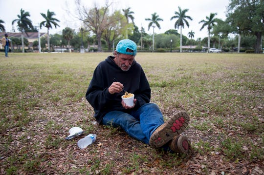 Francis Covati eats while trying to keep his distance from others who came to City of Palms Park for a hot meal on Thursday, April 16, 2020. Homeless citizens in Lee County are having a hard time finding places they can legally be right now since parks are closed.