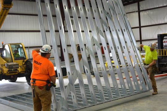Boldt Company employees begin assembling the walls of a STAAT-Mod portable critical care unit at the company's prefabrication facility in the Appleton area.