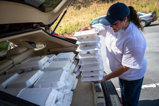 Jackie Souder, who works in the administrative office of Upstate Medical Associates in Seneca, loads plates of food into the back of a car to be delivered to the Utica Mill in Seneca Friday, April 17, 2020, in response to the EF3 tornado which touched down in the early hours of Monday, April, 13.