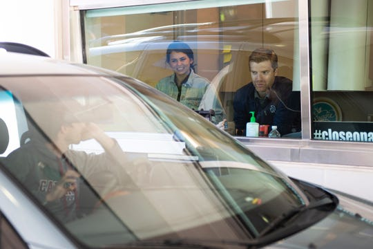 Holliday Ingram Real Estate Law's Trey Ingram (from right) and Blake Roth help Brian Darnell at the drive-thru for law firm in Greenville Thursday, April 16, 2020.
