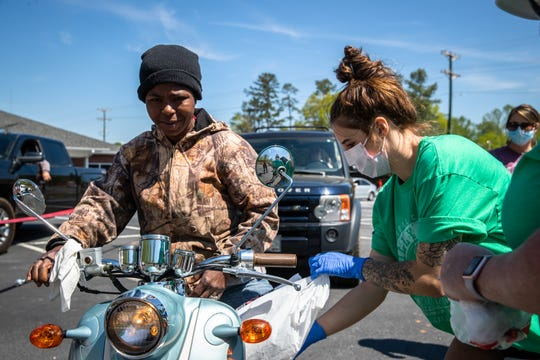 Emily Barker, a nurse assistant at Upstate Medical Associates in Seneca, loads plates of food prepared by Anderson's Texas Roadhouse onto a driver's moped at a drive-thru meal donation at the medical clinic beside the BorgWarner plant, Friday, April 17, 2020, in response to the EF3 tornado which touched down in the early hours of Monday, April, 13.