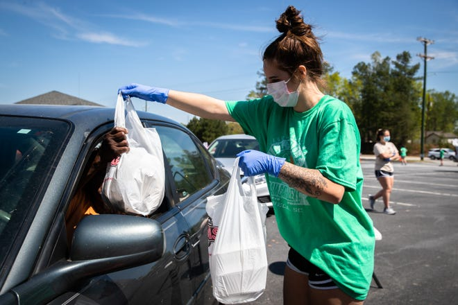 Emily Barker, a nurse assistant at Upstate Medical Associates in Seneca, hands plates of food prepared by Anderson's Texas Roadhouse to a driver at a drive-thru meal donation at the medical clinic beside the BorgWarner plant, Friday, April 17, 2020, in response to the EF3 tornado which touched down in the early hours of Monday, April, 13.