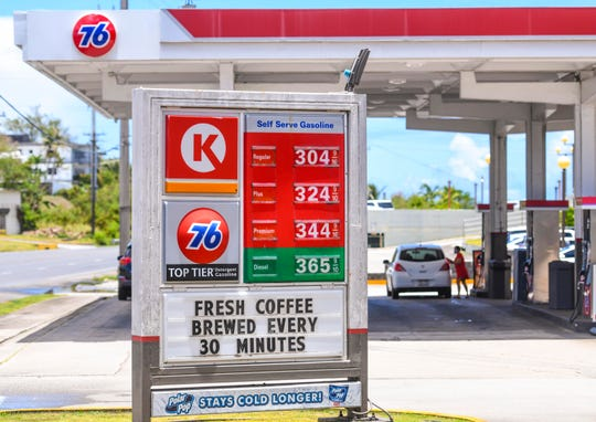 A drop in gasoline prices is reflected on a sign at the Circle K/76 gas station in Sinajana as a customer refuels her vehicle at the business on Friday, April 17, 2020.