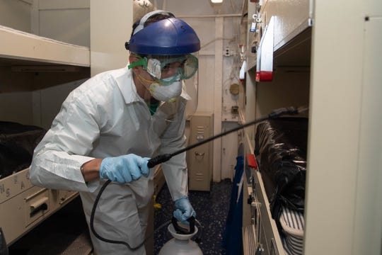 Petty Officer 3rd Class Kyle Hernandez, from Denton, Texas, disinfects a berthing aboard the aircraft carrier USS Theodore Roosevelt with a multi-surface sanitizer on April 12.