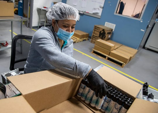 Employee Hope Juarez boxes up bottles of Sugar Creek hand sanitizer at an Indy E Cigs warehouse space in Indianapolis on Wednesday, April 15, 2020. Shadi Khoury owns 11 Indy E Cigs retail vaping stores, deemed non-essential, and was forced to close due to coronavirus. Now he has begun using his facilities to bottle hand sanitizer, some of which is being donated and some being sold publicly.