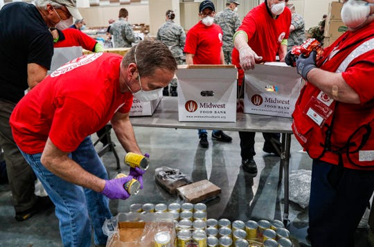 Members from the Salvation Army and Indiana National Guard pack up to 10,000 boxes in two days at Lucas Oil Stadium, Indianapolis, Friday, April 17, 2020. The food boxes will be filled with shelf-stable items designed to help supplement the pantries of families who are struggling due to COVID-19 shut-downs.