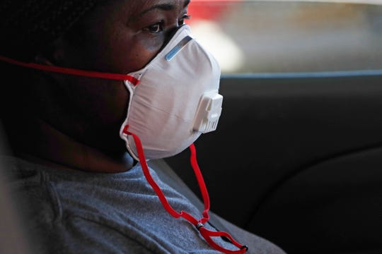 A masked drive-up patient awaits a member of the Delta Health Center staff administering a free COVID-19 test in Mound Bayou, Miss., Thursday, April 16, 2020. The city is predominately African American and recent reports are that black Americans are dying of COVID-19 at disproportionately high rates in some areas.