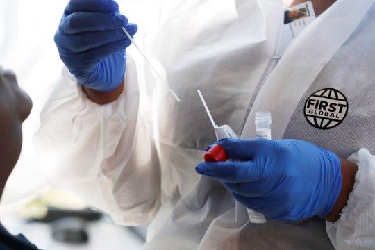 Nurse Ashley Jones prepares to administer a COVID-19 test at the Delta Health Center's Dr. H. Jack Geiger Medical Center in Mound Bayou, Miss., Thursday, April 16, 2020.