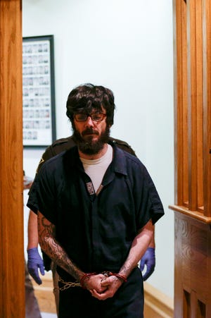 Andrew Alcorns, 41, is escorted into Circuit Court by sheriff's deputies before a hearing with Tippecanoe circuit judge Sean Persin, Friday, April 17, 2020 in West Lafayette. Alcorns is charged with felony murder, attempted murder, aggravated battery and arson in the April 7, 2019, death of Ron Whiles, the stabbing of Whiles' housemate, Tom Day, after which prosecutors say he set fire to their 31st Street home.