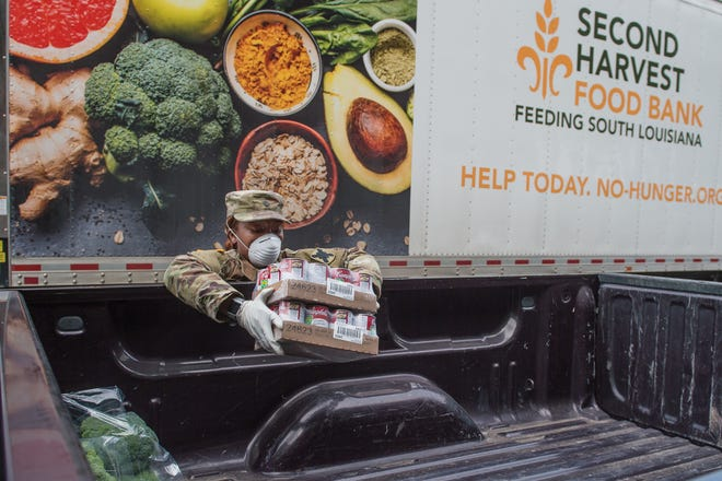 Spc Fontenette from the 256th National Guard distributing food. UL Lafayette in partnership with Second Harvest Food Bank and United Way of Acadiana open a drive-thru food distribution site at Cajun Field for people experiencing economic hardship during the COVID-19 outbreak. Friday, April 17, 2020.