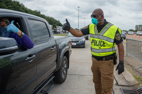 Lt D Zachary from UL Police assisting motorist waiting in line. UL Lafayette in partnership with Second Harvest Food Bank and United Way of Acadiana open a drive-thru food distribution site at Cajun Field for people experiencing economic hardship during the COVID-19 outbreak. Friday, April 17, 2020.