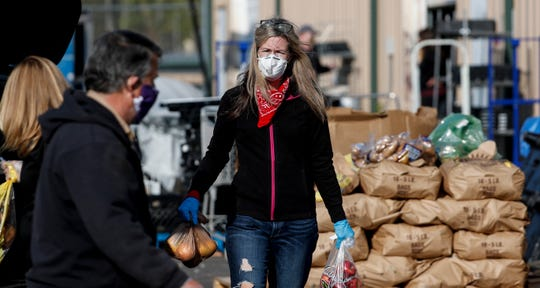 Marcy Bancroft and other volunteers hand out free groceries at HighPoint Charitable Services in LaGrange on April 16, 2020.