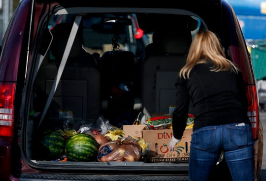 Leigh Ann Gutermuth hand out free groceries at HighPoint Charitable Services in LaGrange on April 16, 2020.