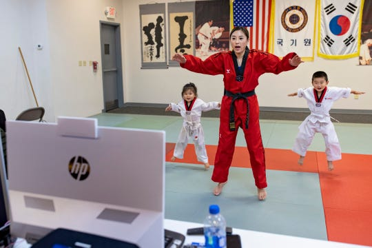 Mimi Hwang with Hwang's Martial Arts teaches an online martial arts class for three to five year olds with her children.