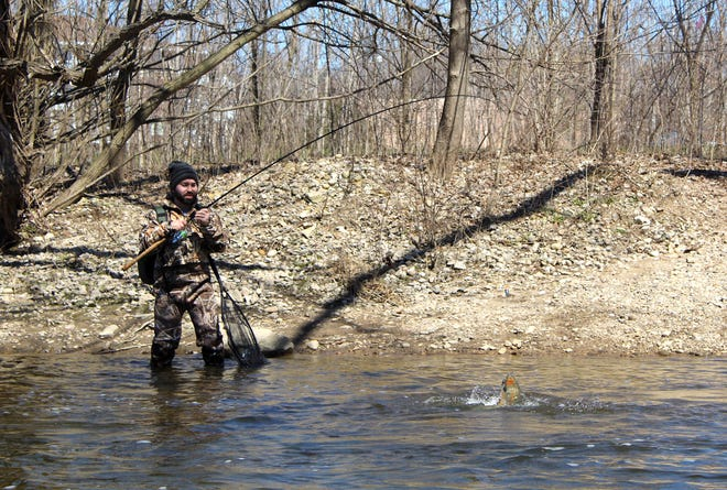 Seth Fisher of West Allis fights a steelhead on the Menomonee River in Wauwatosa.