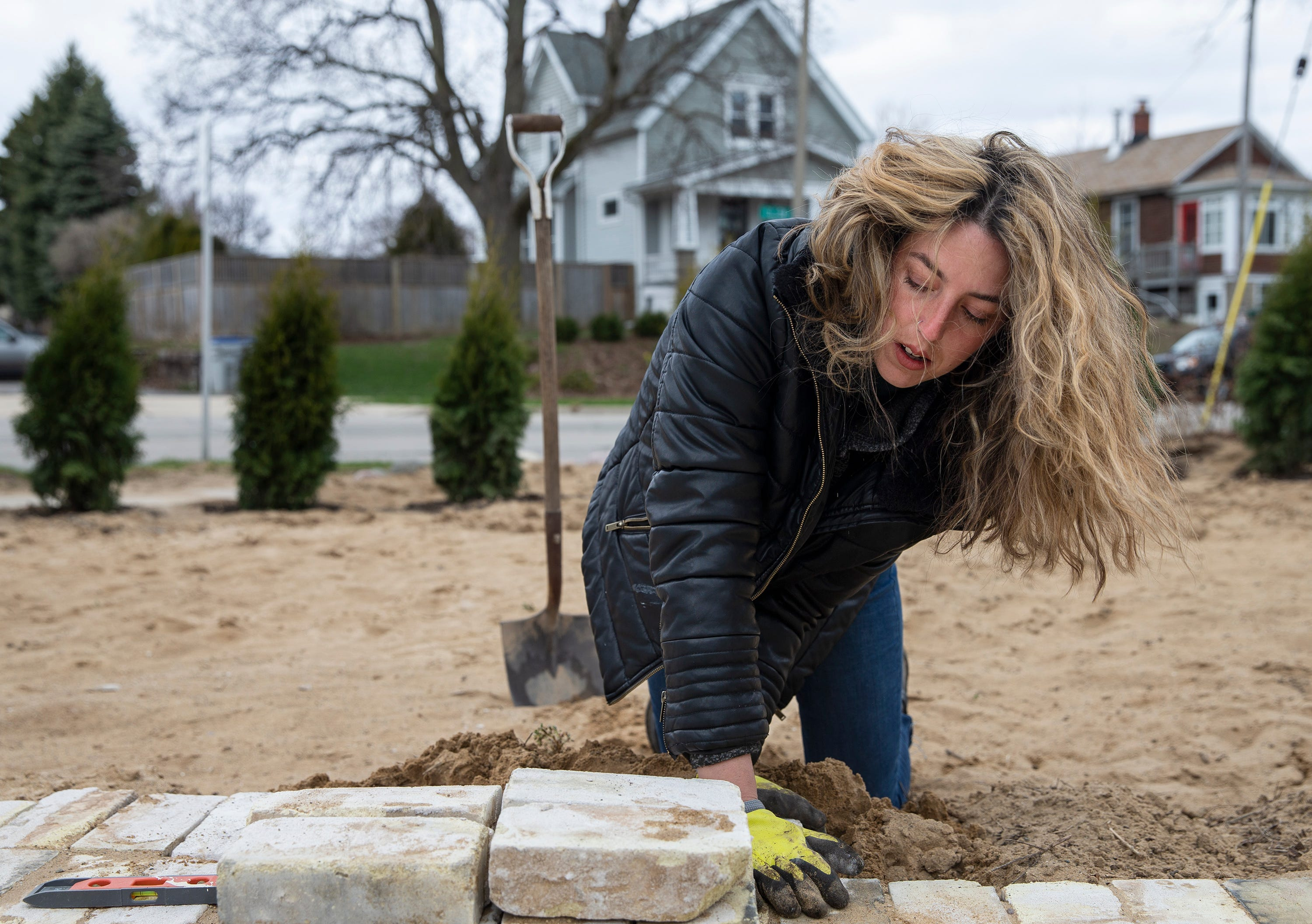 Allison Meinhardt places pavers in the backyard of White House Tavern. The back area will be a patio when it's done.