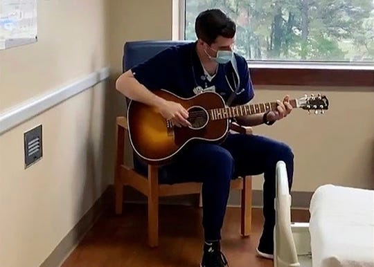 In this March 2020 image taken from video provided by Adam Blackerby, Michael Stramiello plays the guitar inside a hospital room in Benton. In a time of anxiety and isolation, simple acts of kindness from hospital workers are giving comfort to patients and their families. Stramiello plays and sings for stressed-out staffers and patients.