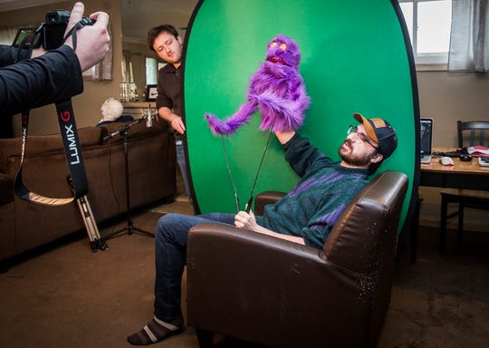Max Cseresznyes (left) holds a green screen while Nicholas Rohrman operates a puppet while filming a video in their apartment on University Avenue Friday, April 17, 2020.