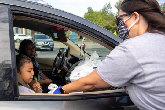Paragon Mills Elementary School principal Dr. Shawnna Pierce hands books from Book'em to a child at Paragon Mills Elementary Friday, April 17, 2020, in Nashville, Tenn.