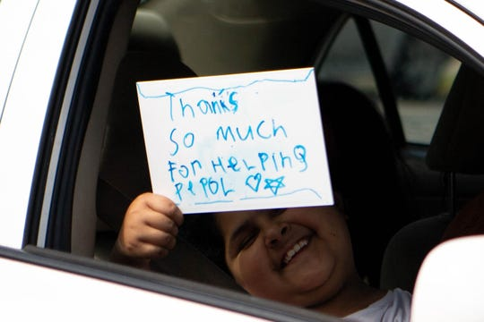 A child holds up a sign while in the line to receive food and books from Book'em at Paragon Mills Elementary School Friday, April 17, 2020, in Nashville, Tenn.