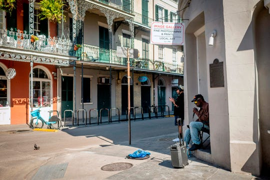 A man sings on a corner of the nearly deserted French Quarter in New Orleans, Louisiana, on March 26, 2020.