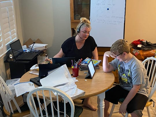 Barron Collier High School teacher Michele Schrier helps her son, Owen, with his online learning while working on her own tasks. Her family modified their dining room to be a shared classroom.