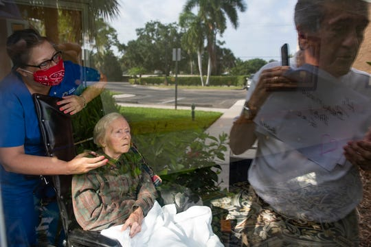 Solaris unit manager Lisa Turner holds a phone for Sharon Duross, 74, as her husband, Bob Duross, communicates with her using his phone and handwritten notes, during a visit, Friday, April 17, 2020, at Solaris Senior Living in North Naples.