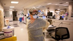 NCH Healthcare System RN Beth Davis dons on her personal protective equipment before treating a patient Friday, April 17, 2020, at NCH Baker Hospital in Naples.