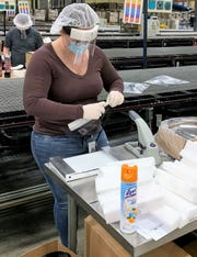 Megan Dulebohn, of Alene Candles, works on making face shields at the company's New Albany facility in Licking County.