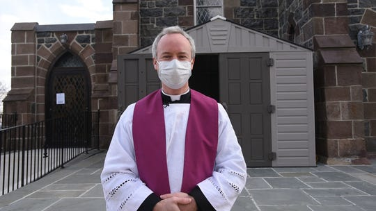 Rev. Daniel O'Mullane outside new confession booth in front of  the Our Lady of Mount Carmel church where parishioners can come safely.