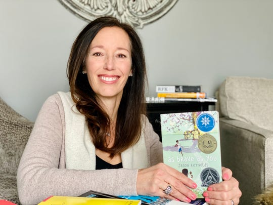 Lisa Erickson, at home with a book she is reading, misses her sixth grade language arts students at Novi Meadows.