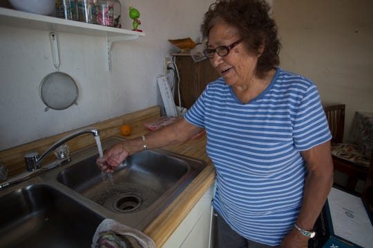 A Navajo woman enjoys hot and cold running water in her home for the first time after receiving a home water/solar panel system from nonprofit DigDeep.
