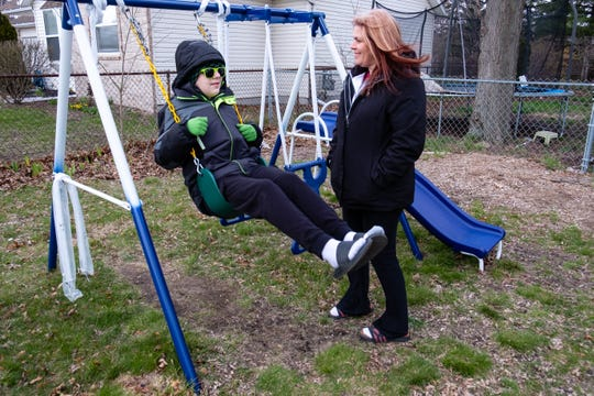 Michelle Kantz, right, watches her son Gabe Norton, 13, who has special needs, play on his swingset Thursday, April 16, 2020, at their home in Port Huron. Kantz, who had trouble getting on unemployment, was worried about how she would care for her son after being laid off from her job at Blue Water Habitat for Humanity due to the coronavirus pandemic.