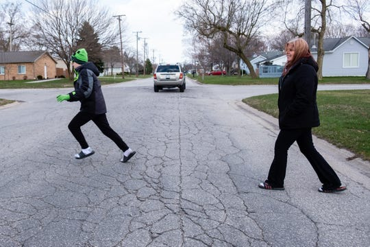 Michelle Kantz, right, crosses the street with her son Gabe Norton, 13, who has special needs, after checking the mail Thursday, April 16, 2020, at their home in Port Huron. Kantz, who had trouble getting on unemployment, was worried about how she would care for her son after being laid off from her job at Blue Water Habitat for Humanity due to the coronavirus pandemic.