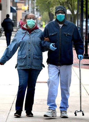 Anthony Ferguson and his partner Elaine Dickson, both of York City, don masks as they walk home on East Market Street after a visit to a bank Friday, April 17, 2020. York City's Hispanic and black populations have the highest percentage of York County's Covid-19 cases. Bill Kalina photo