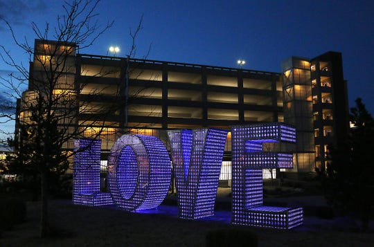 """The statue of the word """"LOVE"""" is seen lit up for the first time at the Renown Regional Medical Center in Reno on April 16, 2020."""