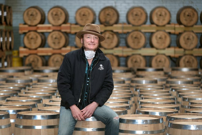 Tommy Brunett, owner of Iron Smoke Distillery, pauses in the Fairport distillery's barrel room. It made hand sanitizer to help in the response to the coronavirus outbreak.