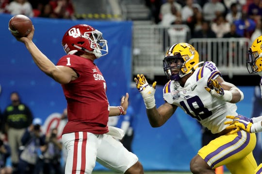 Oklahoma Sooners quarterback Jalen Hurts (1) attempts a pass as LSU Tigers linebacker K'Lavon Chaisson (18) puts on the pressure.