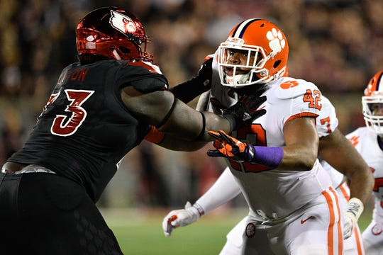 Clemson Tigers defensive lineman Christian Wilkins (42) tries to move past Louisville Cardinals offensive lineman Mekhi Becton.