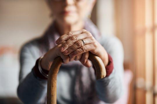 A senior woman holding a cane.