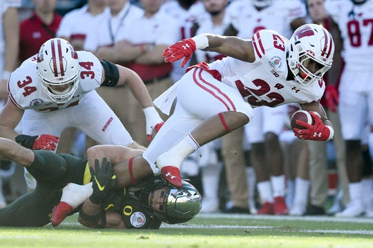 Oregon Ducks safety Brady Breeze (25) tackles Wisconsin Badgers running back Jonathan Taylor (23).