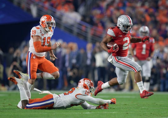 Ohio State Buckeyes running back J.K. Dobbins (2) gets past Clemson Tigers safety K'Von Wallace (12) during the first quarter in the 2019 Fiesta Bowl college football playoff semifinal game.