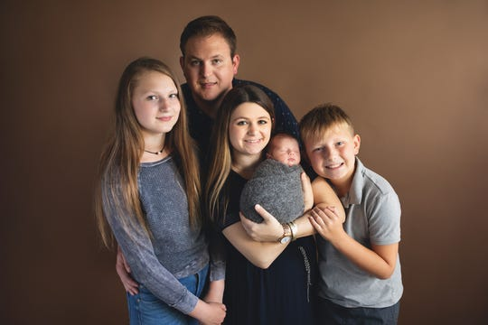 In back, Cameron Johnson recently donated bone marrow to a blood-cancer patient in need of a transplant. To Johnson's right is his 13-year-old daughter, Jaina. To his far left is son Riley, 11. In the middle is Johnson's girlfriend, Ashley Penge, who is holding their newborn son, Jace.